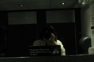 Teresa taking a picture of herself in Calgary Court washroom mirror